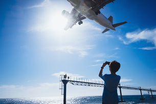 Boy with camera phone photographing airplane flying low overhead near Lanzarote Airportの写真素材 [FYI04324098]