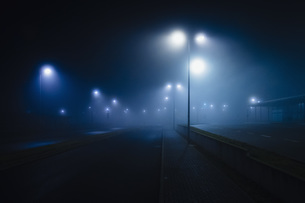 Street lamps illuminated over foggy, vacant roadの写真素材 [FYI04324101]