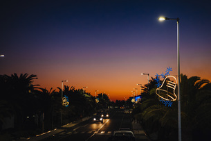 Christmas bell light decorations on street lamps over road at sunset, Costa Teguise, Lanzaroteの写真素材 [FYI04324103]