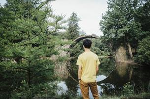 Teenage boy looking at tranquil Rakotzbruecke Devils Bridge, Rakotzbruecke, Brandenburg, Germanyの写真素材 [FYI04324114]