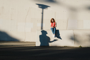 Shadow looking up at young woman using smart phone on urban wallの写真素材 [FYI04324129]