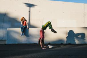Young woman watching man do handstand along urban wallの写真素材 [FYI04324130]