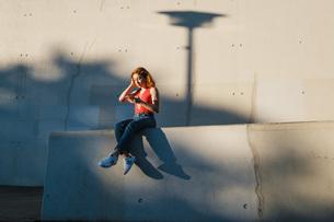 Young woman using smart phone on urban wallの写真素材 [FYI04324131]