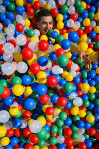 Portrait playful young man laying in multicolor ball poolの写真素材 [FYI04324137]