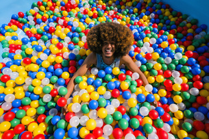 Portrait exuberant young man playing in multicolor ball poolの写真素材 [FYI04324138]
