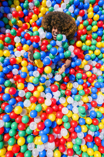 Portrait playful young man in multicolor ball poolの写真素材 [FYI04324139]