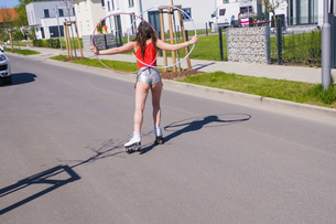 Woman in short shorts with plastic hoops roller skating on sunny neighborhood roadの写真素材 [FYI04324142]