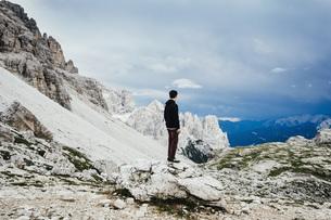 Teenage boy standing on rock overlooking rugged mountains, Drei Zinnen Nature Park, South Tyrolの写真素材 [FYI04324148]