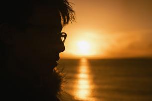 Silhouette profile teenage boy looking at sunset over oceanの写真素材 [FYI04324156]