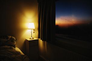 Bedside lamp illuminating bedroom corner next to window with view of dusk skyの写真素材 [FYI04324159]