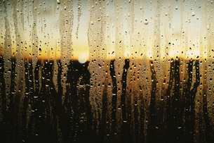 Raindrops and condensation on window with scenic sunset viewの写真素材 [FYI04324160]