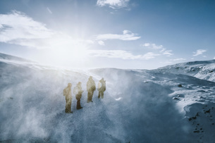 People walking along sunny, windy, snow covered landscape, Reykjadalur, Icelandの写真素材 [FYI04324161]