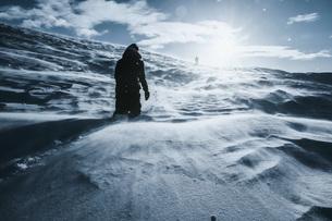 Man walking along sunny snow covered landscape, Reykjadalur, Icelandの写真素材 [FYI04324167]