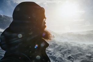Man looking at snowy landscape, Reykjadalur, Icelandの写真素材 [FYI04324168]