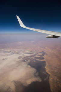 Aerial view airplane wing over landscapeの写真素材 [FYI04324195]