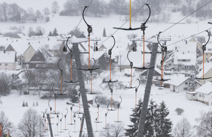 Ski lift cables with ski resort in background, Roemerstein-Donnstetten, Germanyの写真素材 [FYI04324222]