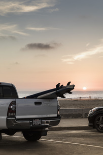 Surfboards in truck bed parked along beach at sunset, Newport Beach, California, USAの写真素材 [FYI04324232]