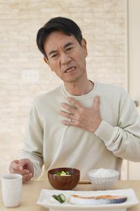 喉を押さえる中年男性の写真素材 [FYI04330974]
