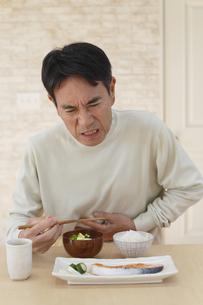 胃痛で顔をゆがめる中年男性の写真素材 [FYI04330976]