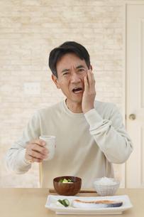 歯痛に顔をゆがめる中年男性の写真素材 [FYI04330982]