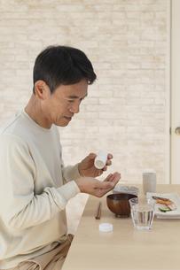 薬を飲む中年男性の写真素材 [FYI04330986]
