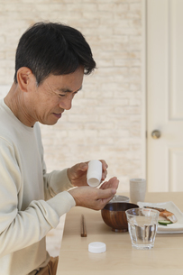 薬を飲む中年男性の写真素材 [FYI04330987]