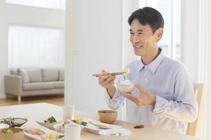朝食を食べる中年男性の写真素材 [FYI04330998]