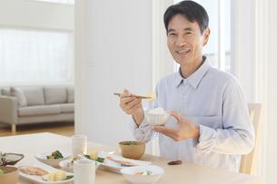 朝食を食べる中年男性の写真素材 [FYI04330999]