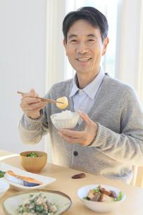 朝食を食べる中年男性の写真素材 [FYI04331001]
