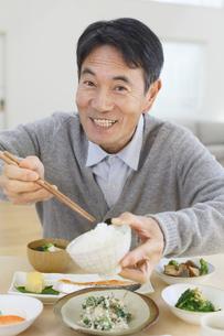 おどけて朝食を食べる中年男性の写真素材 [FYI04331009]
