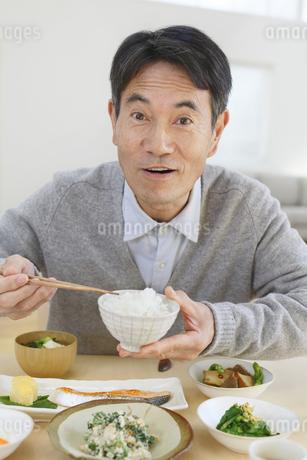 おどけて朝食を食べる中年男性の写真素材 [FYI04331010]