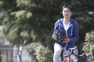 自転車に乗りヘルメットを持つ男性の写真素材 [FYI04332502]