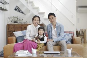 リビングのソファに座る3人家族の写真素材 [FYI04332518]