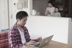 ノートパソコンを見る父親とキッチンの母娘の写真素材 [FYI04332524]