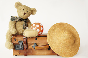 Teddy bear on suit case with hat and ballの写真素材 [FYI04332678]