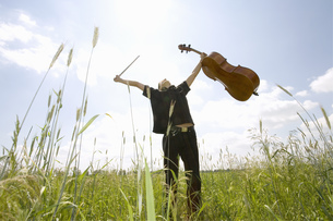 Young man standing in field with cello, low angle viewの写真素材 [FYI04332703]