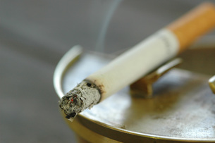 Burning cigarette in ashtray, close-upの写真素材 [FYI04332874]