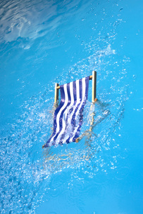 Deck chair falling into a poolの写真素材 [FYI04332894]