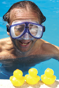 Man in swimming pool looking at plastic ducksの写真素材 [FYI04332906]