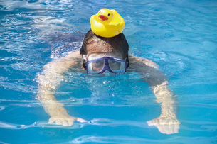 Man swimming with a rubber duck on his headの写真素材 [FYI04332907]