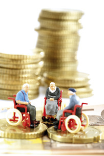 Figurines in wheelchairs on coinsの写真素材 [FYI04332945]