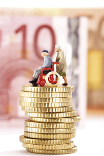 Figurines, senior citizens, on pile of coinsの写真素材 [FYI04332946]