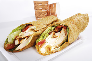 Two wrap sandwiches with white meat and salad, paper cupsの写真素材 [FYI04332986]