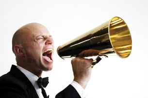 Man shouting into megaphone, side view, close-upの写真素材 [FYI04332989]