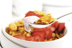 Cornflakes and strawberries on spoon, close-upの写真素材 [FYI04333045]