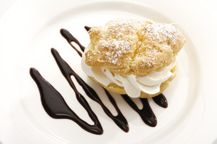 Cream puff with chocolate sauce on plateの写真素材 [FYI04333228]