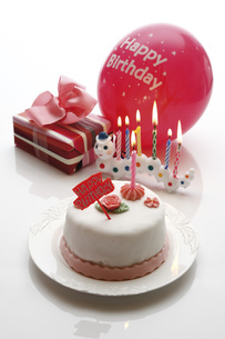 Birthday cake, burning candles and presentの写真素材 [FYI04333421]