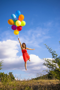 USA, Texas, Young woman flying with balloonsの写真素材 [FYI04333528]