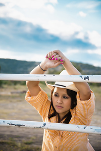 USA, Texas, Young woman leaning on fence, looking awayの写真素材 [FYI04333530]