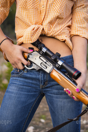 USA, Texas, Young woman standing with hunting rifle, close uの写真素材 [FYI04333531]